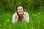 Laughting Frau mit Kopfhörern auf dem Rasen