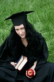 Caucasian Student In Gown With Books
