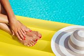 Portrait Of Beautiful Tanned Woman Relaxing In Swimming Pool Spa. Legs And Hands Close Up. Creative poster