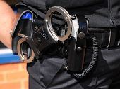 Detail Of Police Utility Belt. Handcuffs And Cs Gas Spray.