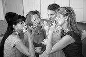 image of foursome  - Unsure young woman around older ladies smoking in the kitchen - JPG
