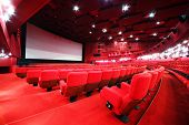 View from stairs on screen and rows of comfortable red chairs in illuminate red room cinema