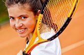 Tenista mujer sosteniendo una raqueta y sonriendo