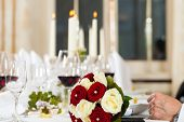 Bouquet at a wedding table; the wedding party is ongoing