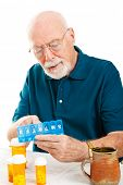 Senior man uses a pill organizer to prepare his medication for the week.  White background.