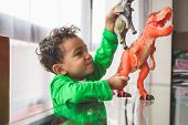 Latin American Kid Playing With Animal Toys At Home . Mixed Race Kid Playing On A Glass Table Indoor poster