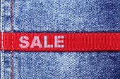 Blue jeans with red label and word SALE