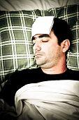Dramática imagen desaturada de un enfermo en cama con fiebre