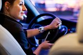 Conducir un coche por la noche - bonita, joven mujer conduciendo su coche moderno por la noche en una ciudad (DOF poco profunda;