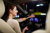 Driving a car at night - pretty, young woman driving her modern car at night in a city (shallow DOF;