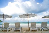 Seascape View Of Beach Facing Out To The Ocean. White Beach Chairs And Umbrellas Put On The Beach. B poster