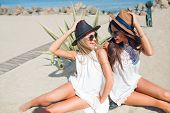 Two Attractive Brunette And Blonde Girls With Long Hair Are Sitting On The Beach Near Sea. They Wear poster