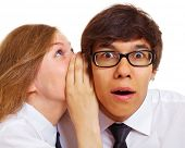 Teenager girl tells something into surprised guy's ear isolated on white background. Mask included
