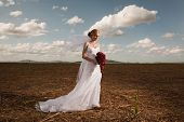 Bride In A Field With Blue Sky And Clouds