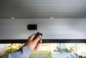 Garage Door Pvc. Hand Uses Remote Controller For Closing And Opening Garage Door poster