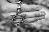 A Hand Of A Young Woman Holding A Key Chain With A Star Of David, Traditional Jewish Symbol. A Conce poster