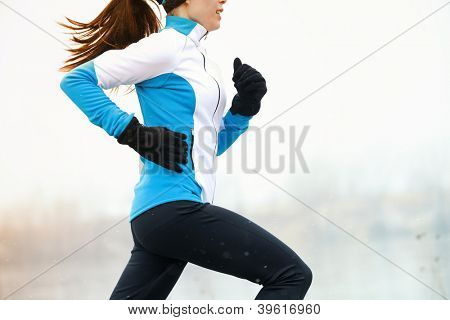 Running athlete woman sprinting during winter training outside in cold snow weather. Close up showin