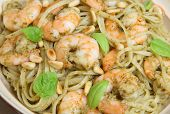 Linguine pasta with shrimps and pesto, garnished with toasted pine nuts and basil leaves.