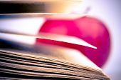 Macro shot of a book pages and blurred apple in the background