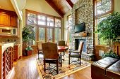 stock photo of stone house  - Luxury mountain home diining and living room with stone fireplace - JPG