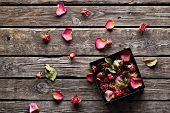 Many rose petals inside open gift box and scattered on old vintage wooden plates. Sweet holiday background with rose petals.