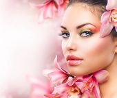 Beautiful Girl With Orchid Flowers.Beauty Model Woman Face. Perfect Skin. Professional Make-up.Makeu