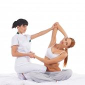 Young woman getting traditional thai stretching massage by therapist isolated on white background