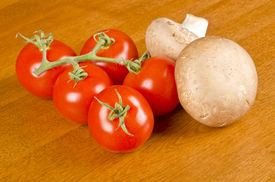 picture of crimini mushroom  - Bunch of vine ripened Campari tomatoes and Crimini mushrooms on table top - JPG