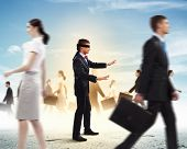 picture of blindfolded man  - Image of businessman in blindfold walking among group of people - JPG