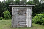 stock photo of outhouses  - an Old Outhouse in the rural meadow - JPG