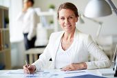 Image of formal businesswoman looking at camera at workplace