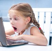 astonished little girl with her computer at home at the table