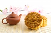 Chinese mid autumn festival foods. Traditional mooncakes on table setting with teapot. The Chinese words on the mooncakes means durian pure lotus paste, not a logo or trademark.