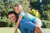 Daughter getting piggy back from dad in a park smiling at camera
