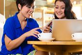 Asian female friends enjoying her leisure time in a cafe, drinking coffee or cappuccino and working