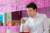 Young man in a cafe or ice cream parlor eating a cake, maybe he is single or waiting for someone