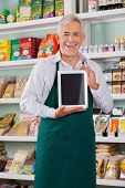 Portrait of happy senior male store owner showing digital tablet in supermarket