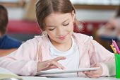 Little schoolgirl smiling while using digital tablet at desk in classroom