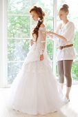 Beautiful young bride wears dress by stylist