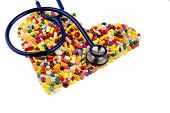 stethoscope and pills in heart-shaped arrangement, symbol photo for heart disease, diagnosis and med
