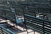 Rows of empty green benches at stadium
