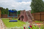 A children slide, trampoline and sandbox on the playground in the country house