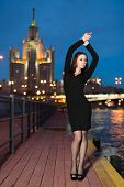 Young woman in black dress standing on the waterfront lifted hands on background night city