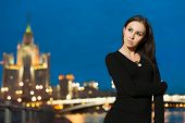 Beautiful young woman in black dress standing on the waterfront in the night city