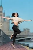 Young woman jumping on the waterfront with outstretched arms to the sides