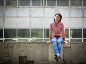 Brunette woman in blue jeans and a pink shirt sitting on a concrete parapet. Real people series