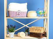 Beautiful white shelves with different home related objects, on color wall background