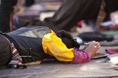 LHASA, TIBET-OCTOBER 08: Tibetan Buddhists pilgrim is praying in full ground prostration in front of
