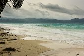 foto of typhoon  - A passing typhoon combined with monsoon winds whips up the sea around a tropical beach - JPG
