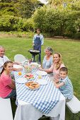 Cheerful extended family having a barbecue outside smiling at camera